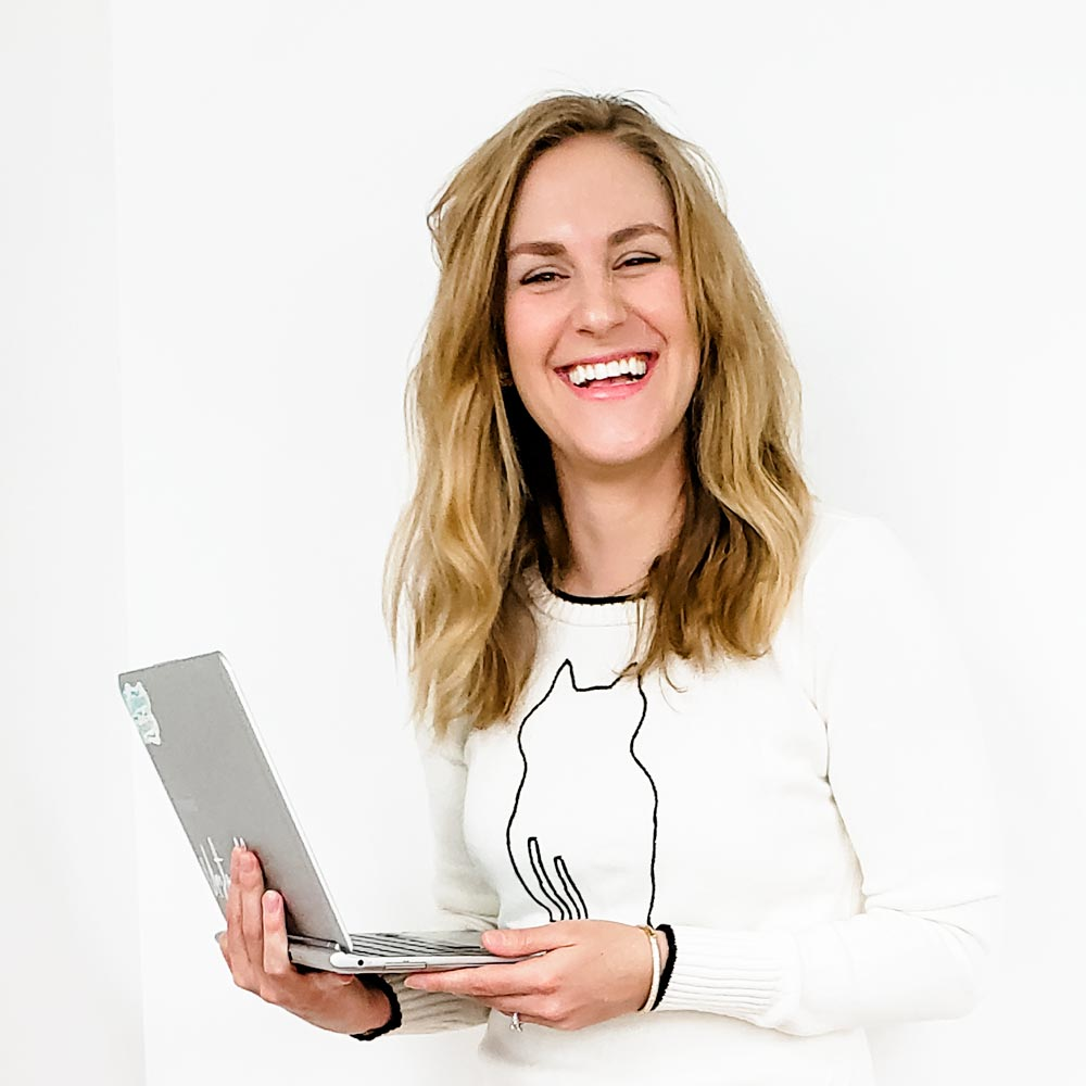 Erin Flynn wearing a cat sweater and holding a computer, laughing, because her husband is being ridiculous out of shot
