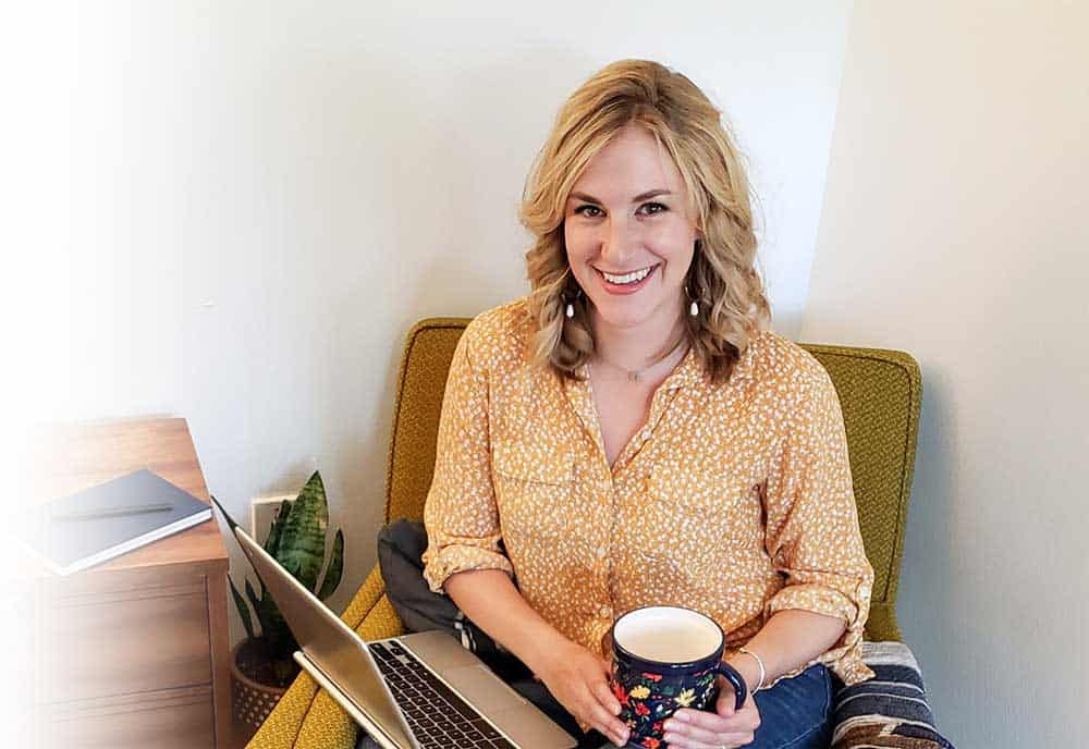 Erin Flynn sitting in a chair with coffee and a computer